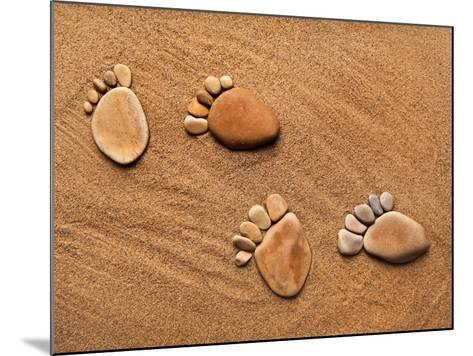 Trace Feet Steps Made Of A Pebble Stone On The Sea Sand Backdrop-Madlen-Mounted Photographic Print