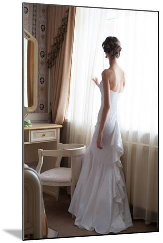 Beautiful Bride in White Wedding Dress Standing in Her Bedroom and Looking in Window- Malyugin-Mounted Photographic Print