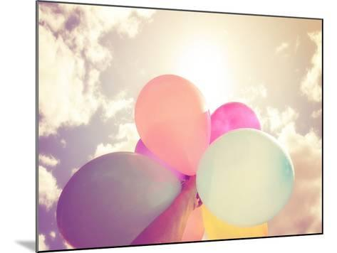 A Person Holding Multi Colored Balloons Done with a Retro Vintage Instagram Filter Effect-graphicphoto-Mounted Photographic Print