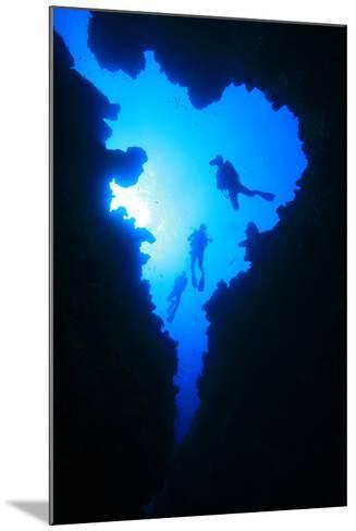 Scuba Divers Descend into Underwater Cavern, Silhouetted against Sun-Rich Carey-Mounted Photographic Print