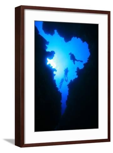 Scuba Divers Descend into Underwater Cavern, Silhouetted against Sun-Rich Carey-Framed Art Print