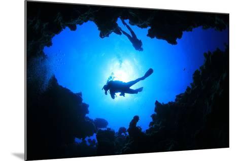 Scuba Divers Descend into an Underwater Cavern. Silhouettes against Sunburst-Rich Carey-Mounted Photographic Print