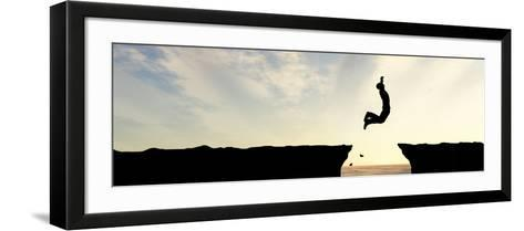 Concept or Conceptual Young Man, Businessman Silhouette Jump Happy from Cliff over Water Gap Sunset-bestdesign36-Framed Art Print