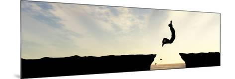 Concept or Conceptual Young Man, Businessman Silhouette Jump Happy from Cliff over Water Gap Sunset-bestdesign36-Mounted Photographic Print