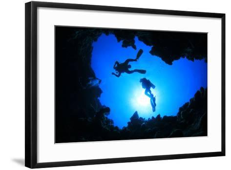 Scuba Divers Descend into an Underwater Cavern. Silhouettes against Sunburst-Rich Carey-Framed Art Print