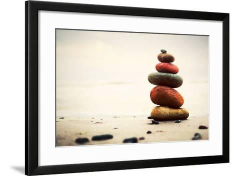 Stones Pyramid on Sand Symbolizing Zen, Harmony, Balance. Ocean in the Background-Michal Bednarek-Framed Art Print
