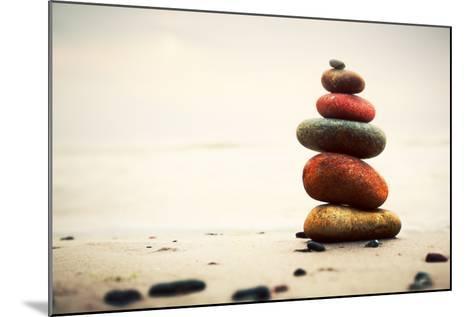 Stones Pyramid on Sand Symbolizing Zen, Harmony, Balance. Ocean in the Background-Michal Bednarek-Mounted Photographic Print