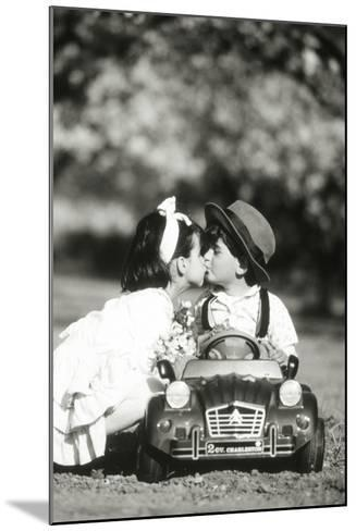 Children Kiss in Toy Car--Mounted Photographic Print