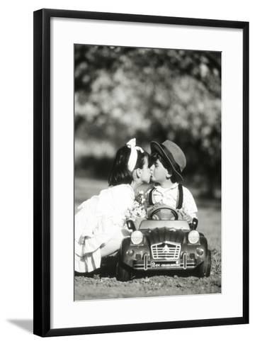 Children Kiss in Toy Car--Framed Art Print