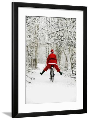 Father Christmas Riding Bicycle in Snowy Woodland Path--Framed Art Print