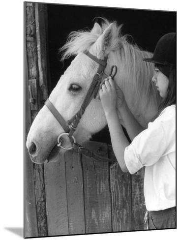 Girl Bridling Horse--Mounted Photographic Print