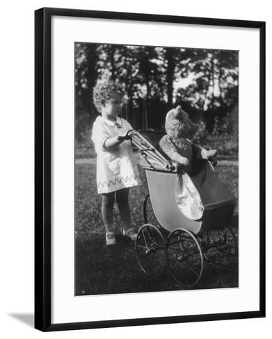 Little Girl Pushes Her Teddy Bear Around in a Pram--Framed Art Print