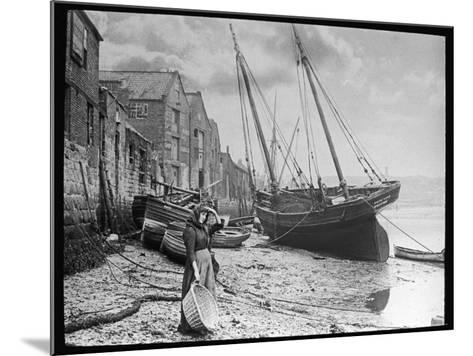 Young Woman in Headscarf and Working Clothes Looks out to Sea from the Shoreline--Mounted Photographic Print