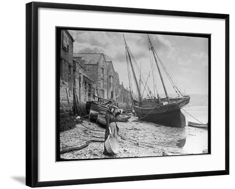 Young Woman in Headscarf and Working Clothes Looks out to Sea from the Shoreline--Framed Art Print