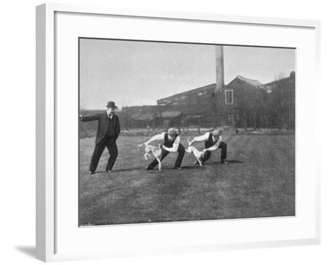 Two Owners Demonstrate How Whippets are Started in a Race : This Is known as 'Flapping'--Framed Art Print