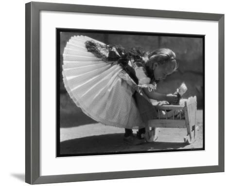 Young Romanian Girl Leans to Pick up Her Small Doll from a Beautifully Crafted Wooden Crib--Framed Art Print