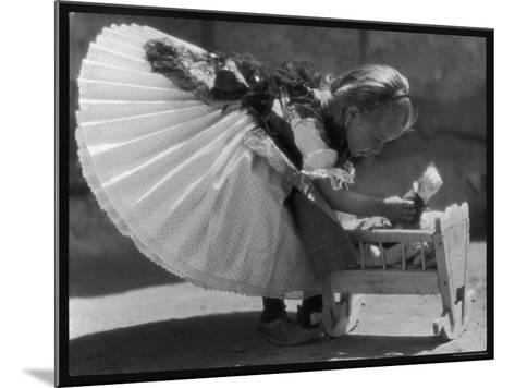 Young Romanian Girl Leans to Pick up Her Small Doll from a Beautifully Crafted Wooden Crib--Mounted Photographic Print