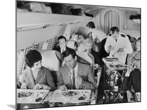 An Airline Steward and Air Hostess Serve a Roast Meal to Flight Passengers--Mounted Photographic Print