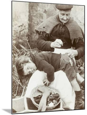 Cornish Grandmother Repairs Her Grandson's Clothing--Mounted Photographic Print