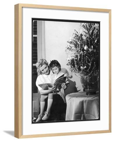 A Little Girl Sits on Her Mother's Knee and Reads a Book Beside the Christmas Tree--Framed Art Print