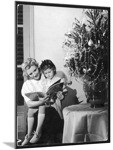 A Little Girl Sits on Her Mother's Knee and Reads a Book Beside the Christmas Tree--Mounted Photographic Print