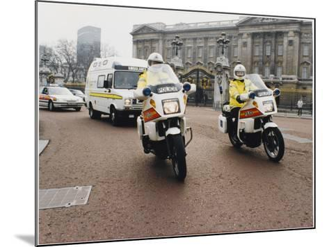 Metropolitan Police Motorcyclists Esccorting an Ambulance Past Buckingham Palace in London--Mounted Photographic Print