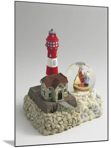 Figurine of a Lighthouse with a Snow Globe--Mounted Photographic Print