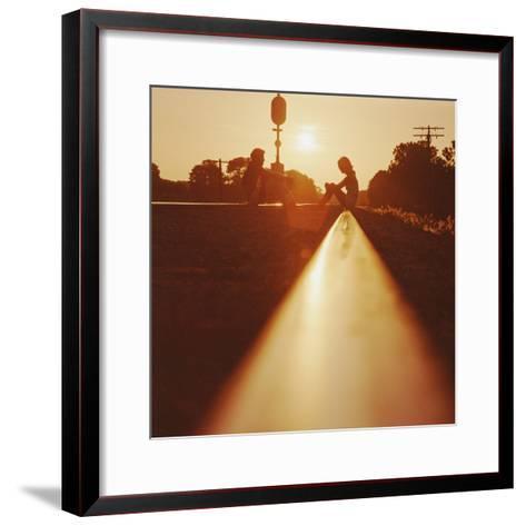 Silhouette of Couple Sitting on Railroad Tracks at Sunset-Dennis Hallinan-Framed Art Print