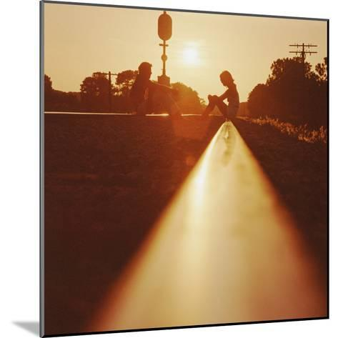 Silhouette of Couple Sitting on Railroad Tracks at Sunset-Dennis Hallinan-Mounted Photographic Print