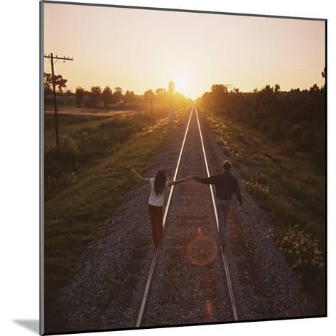 Couple Walking on Railroad Tracks Holding Hands-Dennis Hallinan-Mounted Photographic Print