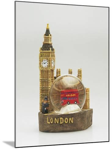 Close-Up of a Toy Bus in a Snow Globe in Front of a Figurine of a Clock Tower--Mounted Photographic Print