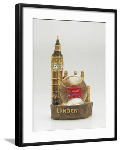 Close-Up of a Toy Bus in a Snow Globe in Front of a Figurine of a Clock Tower--Framed Art Print