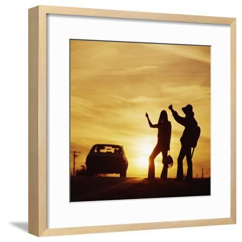 Silhouetted Couple Hitchhiking on Roadside-Dennis Hallinan-Framed Art Print
