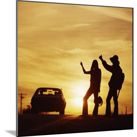 Silhouetted Couple Hitchhiking on Roadside-Dennis Hallinan-Mounted Photographic Print