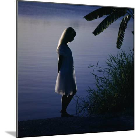Silhouette of woman standing near a lake-Dennis Hallinan-Mounted Photographic Print
