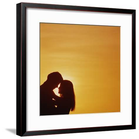 Silhouette of couple embracing at sunset-Dennis Hallinan-Framed Art Print