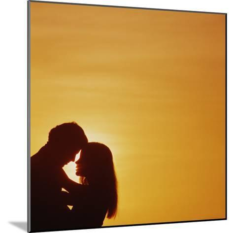 Silhouette of couple embracing at sunset-Dennis Hallinan-Mounted Photographic Print