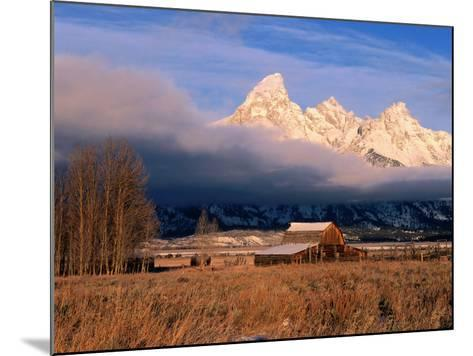 View of Historic Old Barn and Snow-Covered Teton Mountain Range-Jeff Foott-Mounted Photographic Print