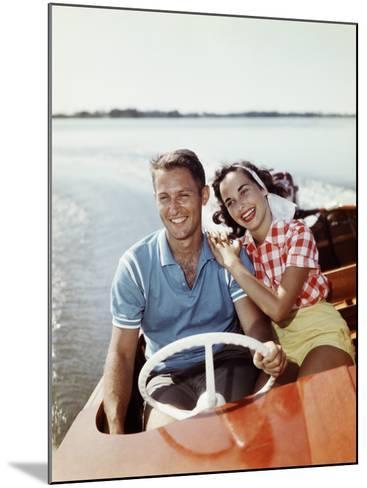 Smiling Retro Couple Enjoying a Speed Boat Ride-Dennis Hallinan-Mounted Photographic Print