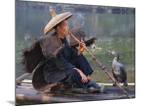 China, Guangxi Province, Yangshuo, Fisherman Smoking a Pipe on the Bamboo Raft on the Li River-Keren Su-Mounted Photographic Print