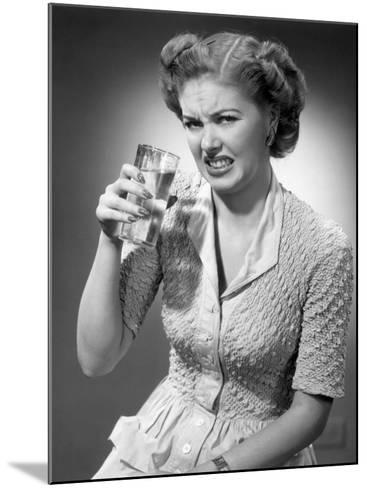 Woman Drinking Glass of Water With Look of Disgust-George Marks-Mounted Photographic Print