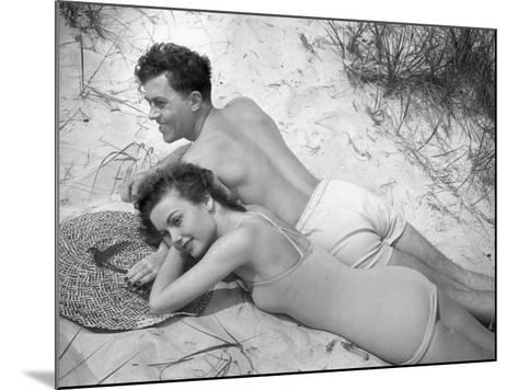 Young Couple in Bathing Suits Lying on Sand-George Marks-Mounted Photographic Print