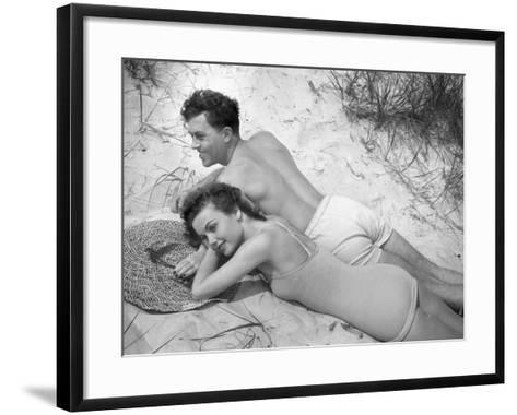 Young Couple in Bathing Suits Lying on Sand-George Marks-Framed Art Print
