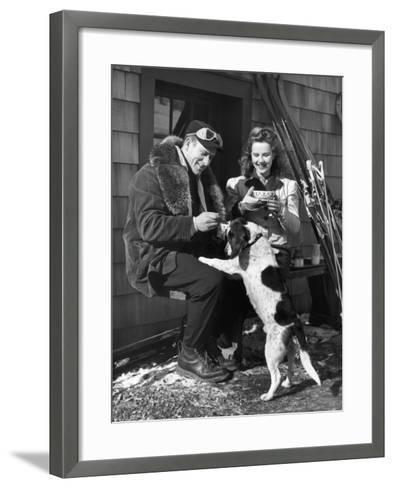 Couple With Dog in Front of Ski Lodge-George Marks-Framed Art Print