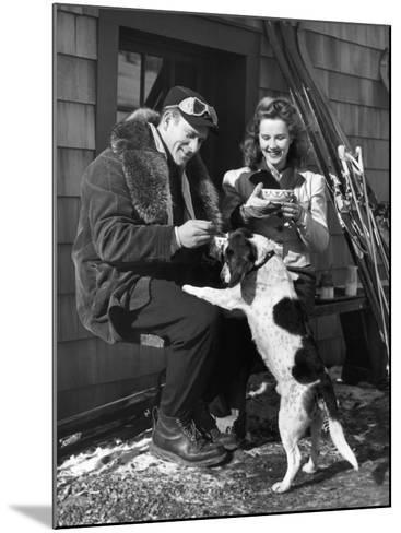 Couple With Dog in Front of Ski Lodge-George Marks-Mounted Photographic Print
