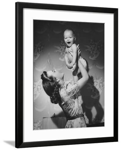 Woman Lifting Up Baby (6-9 Months) at Home-George Marks-Framed Art Print