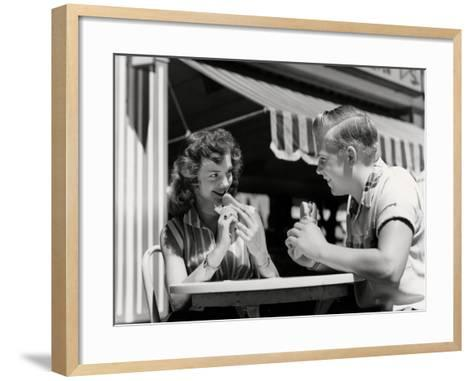 Teenage Couple Eating Hotdogs Outside at Refreshment Stand Table-H^ Armstrong Roberts-Framed Art Print