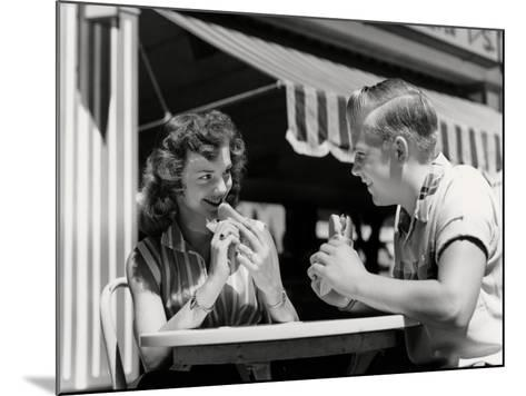 Teenage Couple Eating Hotdogs Outside at Refreshment Stand Table-H^ Armstrong Roberts-Mounted Photographic Print