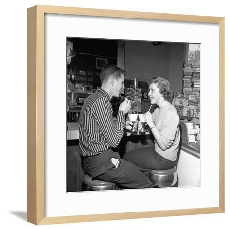 Teen Couple on Stools at Soda Fountain Drinking Shakes and Smiling at Each Other-H^ Armstrong Roberts-Framed Art Print