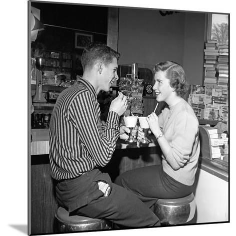 Teen Couple on Stools at Soda Fountain Drinking Shakes and Smiling at Each Other-H^ Armstrong Roberts-Mounted Photographic Print